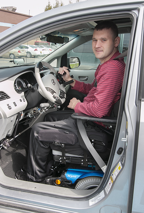 John secures his motorized wheelchair as he prepares to drive a van equipped with hand controls